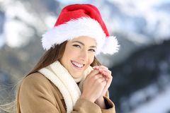 Woman on christmas holidays looking at you. Smiley woman on christmas holidays looking at you with a snowy mountain in the background Royalty Free Stock Images