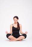 Smiley woman doing yoga exercise. Smiley woman in black sportswear doing yoga exercise Stock Image