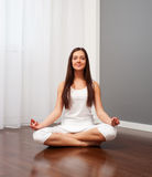 Smiley woman doing yoga in room Stock Photo