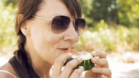 Smiley woman eats an watermelon outdoors on summer. Sunny day. Eating fruits outdoors on a picnic is a popular way of spending weekends. The female is wearing royalty free stock photo
