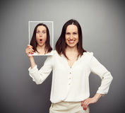 Smiley woman hiding her amazement Stock Photo