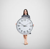 Smiley woman holding big white clock Stock Photography