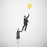 Smiley woman holding flying man Stock Image