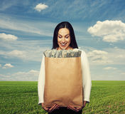 Smiley woman holding paper bag with money. Amazed and smiley woman holding paper bag and looking at money over green field and blue sky royalty free stock photos