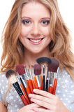 Smiley woman with make-up tools Royalty Free Stock Image