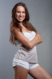 Smiley woman in pajamas against grey background. Smiley young woman with long drown hair in pajamas posing against grey background Royalty Free Stock Photo