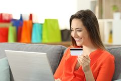 Smiley woman paying on line with credit card. Sitting on a couch in the living room at home Stock Photos