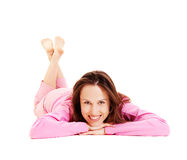 Smiley woman in pink pyjamas lying on the floor Royalty Free Stock Image