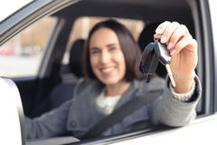 Smiley woman showing the car keys. Smiley woman sitting in car and showing the car keys. focus on the keys Royalty Free Stock Image