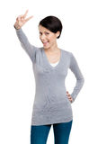 Smiley woman shows peace sign Stock Photography