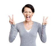 Smiley woman shows peace sign with two hands Stock Photos