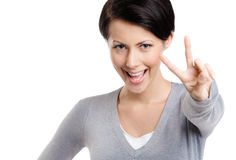 Smiley woman shows victory sign. Isolated on white Royalty Free Stock Images