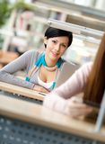 Smiley woman sits at the desk. Behind another one at the reading hall Royalty Free Stock Image