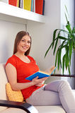 Woman sitting on couch and holding the book stock image
