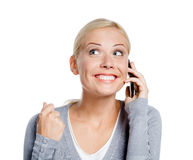 Smiley woman speaking on phone. With her fist up, isolated on white Royalty Free Stock Photo