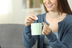 Smiley woman throwing sugar into coffee mug at home. Close up of a smiley woman throwing sugar into coffee mug sitting on a couch in the living room at home Stock Image
