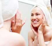 Smiley woman in towel looking in mirror Royalty Free Stock Images