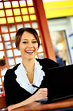 Smiley woman using laptop at the cafe Stock Photo
