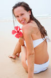 Smiley woman in white swimsuit sitting Stock Photo