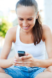 Smiley woman writing text message Stock Photo