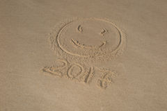 Smiley and writing on sand numeral 2017 near sea with waves. Stock Photography