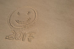 Smiley and writing on sand numeral 2017 near sea with waves. Stock Image