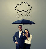Smiley young couple with black umbrella Royalty Free Stock Photo