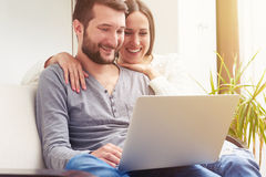 Smiley young couple sitting on sofa Stock Photos