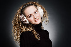 Smiley young girl in fur headphones. Over dark background Royalty Free Stock Image