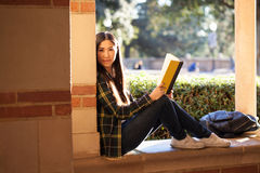 Smiley young girl sitting on the window at the university terrac. E with a book in her hands looking straight to the camera Royalty Free Stock Photos