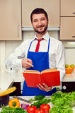 Smiley young man pointing at the cookbook Stock Photography
