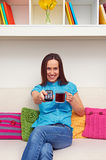 Woman holding cup of tea and remote controller Royalty Free Stock Photo