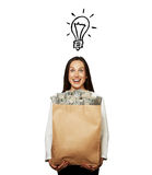 Smiley young woman with paper bag. Smiley young woman with drawing light bulb holding paper bag with money over white background Stock Photos