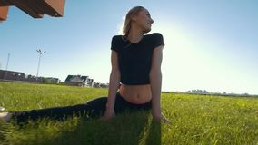 Smiley young woman performs the twine outdoors under the sun. Slow motion stock video
