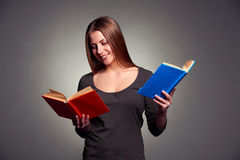 Smiley young woman reading the books. Studio shot over dark background Royalty Free Stock Photo