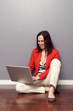 Woman sitting on the floor and using laptop Stock Photos