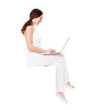 Smiley young woman sitting with laptop Royalty Free Stock Photo