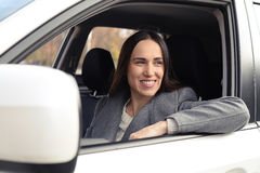 Smiley young woman in the white car Stock Image
