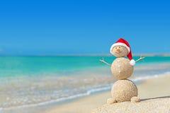 Smiley zandige sneeuwman in santahoed Vakantieconcept voor Nieuwjaren Stock Fotografie