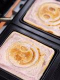 Smileyblaubeerpfannkuchen, die auf Sandwichhersteller kochen Lizenzfreie Stockfotografie