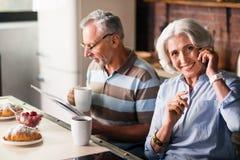 Smileyen avgick par som har morgonkaffe i köket arkivbilder
