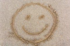 Smileyframsida som dras i sanden från över arkivbilder