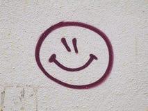 Smileyframsidagrafitti som dras på väggen Arkivfoto