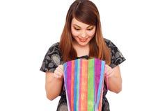 Smileyfrau, die zur Einkaufstasche schaut Stockbilder
