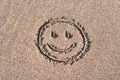 Smileygesicht gezeichnet auf Strandsand stockfotografie