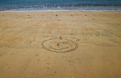 Smileygesicht mit Meer hinten, gezeichnet in den goldenen Sand von kleinem stockfotografie
