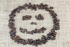 Smileygesicht völlig gemacht aus den Kaffeebohnen heraus gesetzt auf Kaffee Stockbild