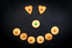 Smileygezicht van kinderachtige koekjes op zwarte achtergrond Royalty-vrije Stock Afbeeldingen