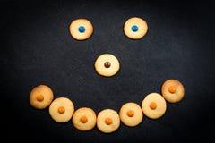 Smileygezicht van kinderachtige koekjes op zwarte achtergrond Royalty-vrije Stock Foto's