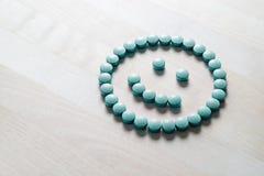 Smileygezicht van pillen op houten lijst Stock Afbeelding